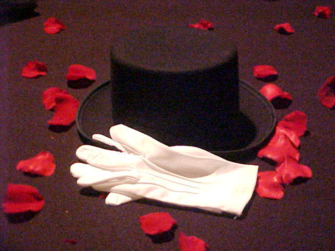 Black top hat with white gloves and rose petals