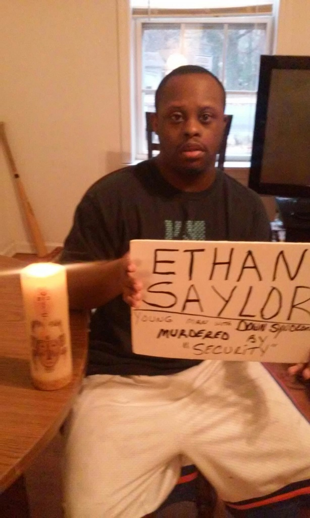 """Dude"" holding sign that says Ethan Saylor beside a lit candle"