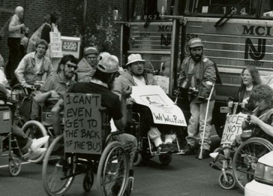 """I can't even get to the back of the bus."" ADAPT activists protesting for accessible transportation, Philadelphia, 1990. [Smithsonian National Museum of American History]"