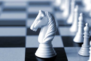 White knight on a chess board.  Shallow depth of field, blue duotone.